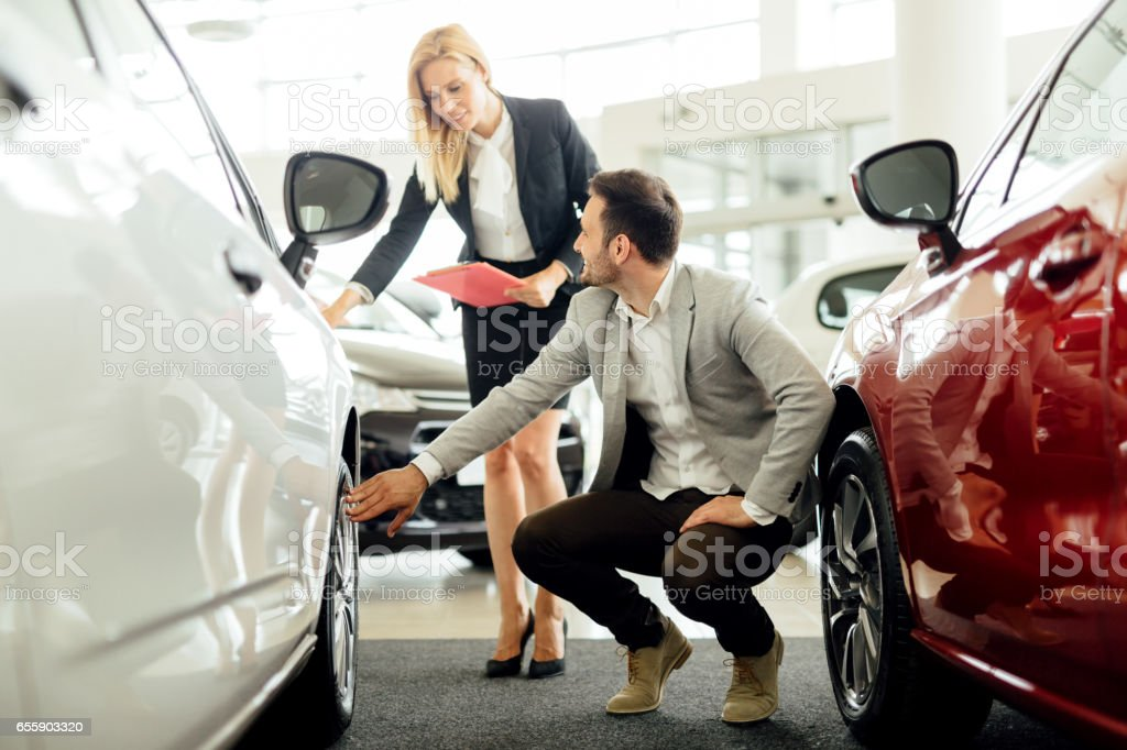 Car salesperson explaining tire and rim options stock photo