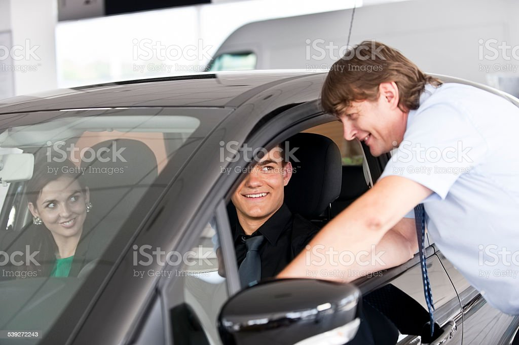Car salesperson showing customers a new car stock photo