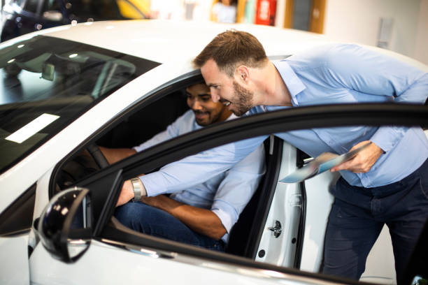 Autoverkäufer zeigt einem Kunden in einem Autohaus die neuen Fahrzeugmodellmerkmale – Foto