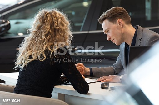 136591825istockphoto Car salesperson talking with customer in showroom 858745034