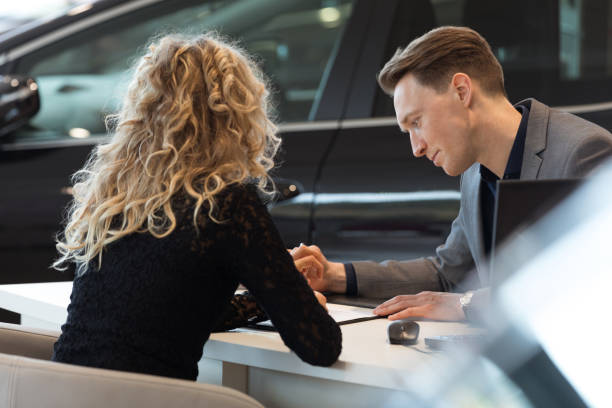 Car salesperson talking with customer in showroom Car salesperson talking with female customer while sitting at desk in showroom car salesperson stock pictures, royalty-free photos & images