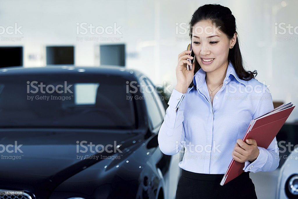 Car saleswoman is on the phone royalty-free stock photo
