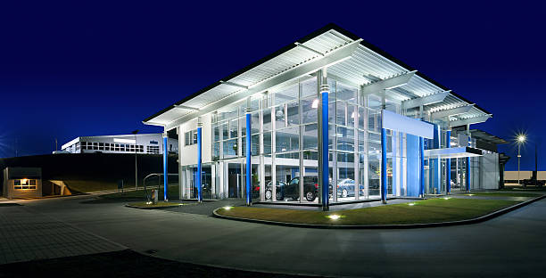 Car Salon Exterior of a modern car salon, night scene. showroom stock pictures, royalty-free photos & images