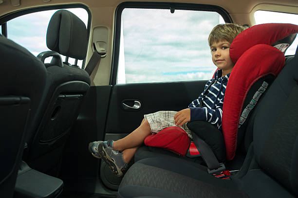 Car seat Little boy sitting in high back booster car seat fasten with seat belt. Child safety. seat stock pictures, royalty-free photos & images