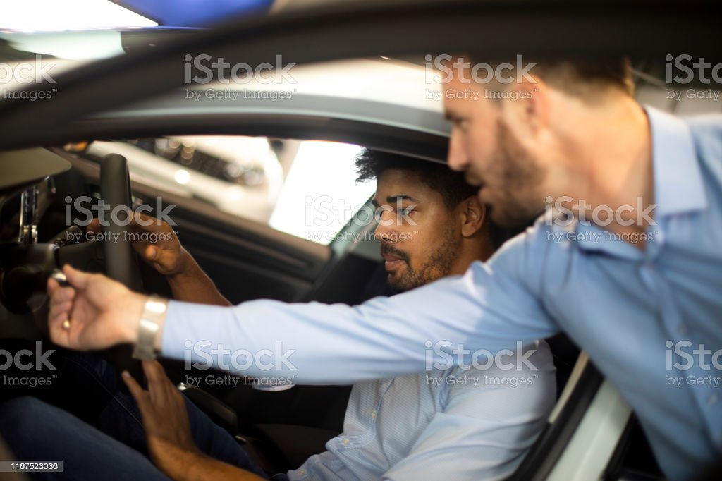 Car merchant demonstrating some turn signal lever controls to a...