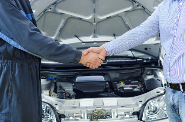 Car service. Mechanic and customer shaking hands. Excellent cooperation between car mechanic and customer. auto mechanic stock pictures, royalty-free photos & images