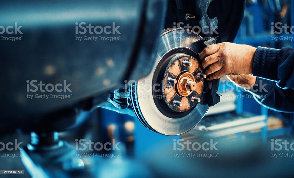 Closeup of unrecognizable mechanic replacing car brake pads. The car...