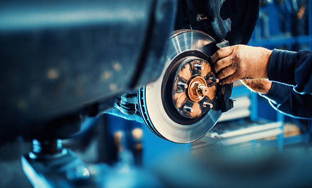 Car service procedure. Closeup of unrecognizable mechanic replacing car brake pads. The car is lifted with hydraulic jack at eye level. mechanic stock pictures, royalty-free photos & images