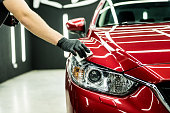 istock Car service worker applying nano coating on a car detail. 1273682054