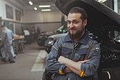 istock Car service worker repairing automobile 1151753130