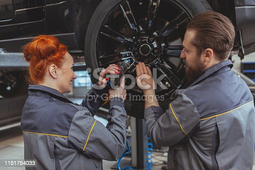 istock Car service worker repairing automobile 1151754033