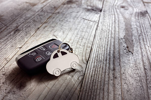 Car shape keyring and keyless entry remote Car shape keyring and keyless entry remote on wood background car key stock pictures, royalty-free photos & images