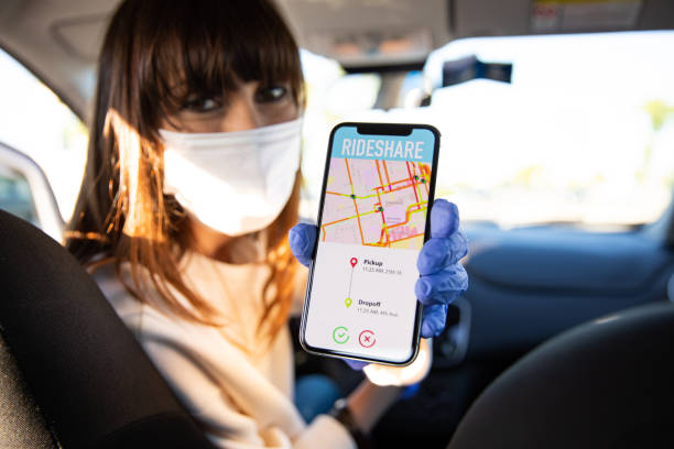 Car sharing driver showing destination to passengers on smart phone stock photo