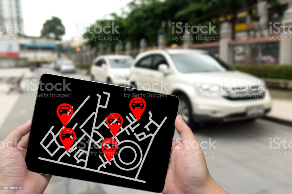 Car sharing service or rental concept. Sharing economy and collaborative consumption. Man hand holding tablet with icons application screen and blur car park background. stock photo
