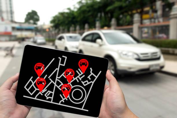 Concept de location ou de service d'autopartage. Partage de l'économie et la consommation collaborative. L'homme de main tenant la tablette avec écran icônes de l'application et parking arrière-plan flou. - Photo
