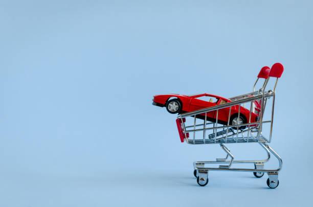 Car shopping, new car in a shopping cart stock photo