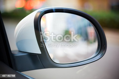 Close-up of a car Side Rear View Mirror with City Street View in Reflection.