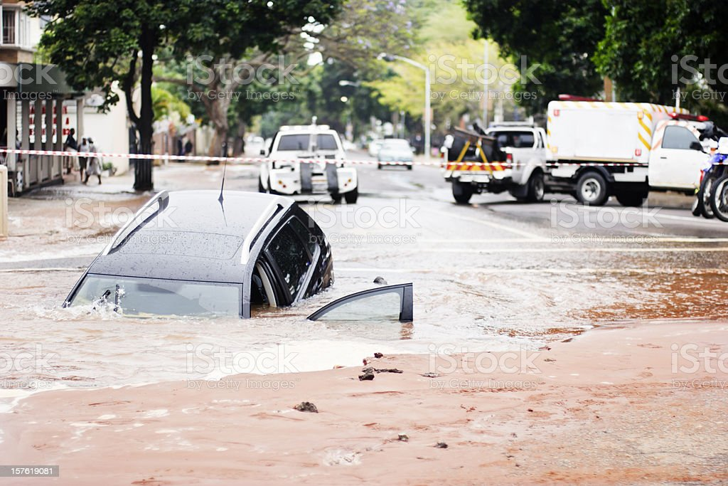 Car sinks into pothole in flooded urban road stock photo