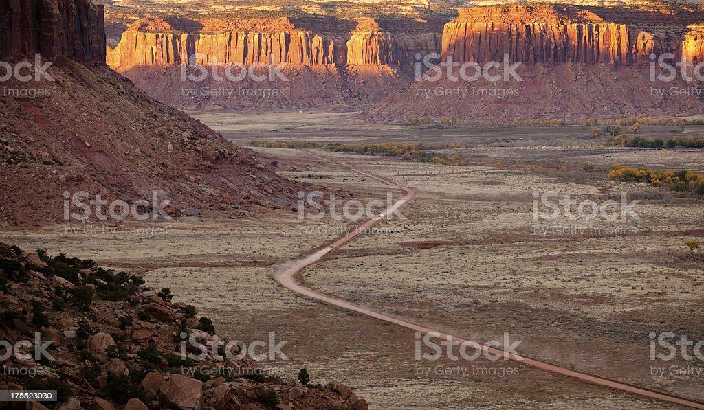 Car speeding down dusty desert road in Utah at sunset stock photo