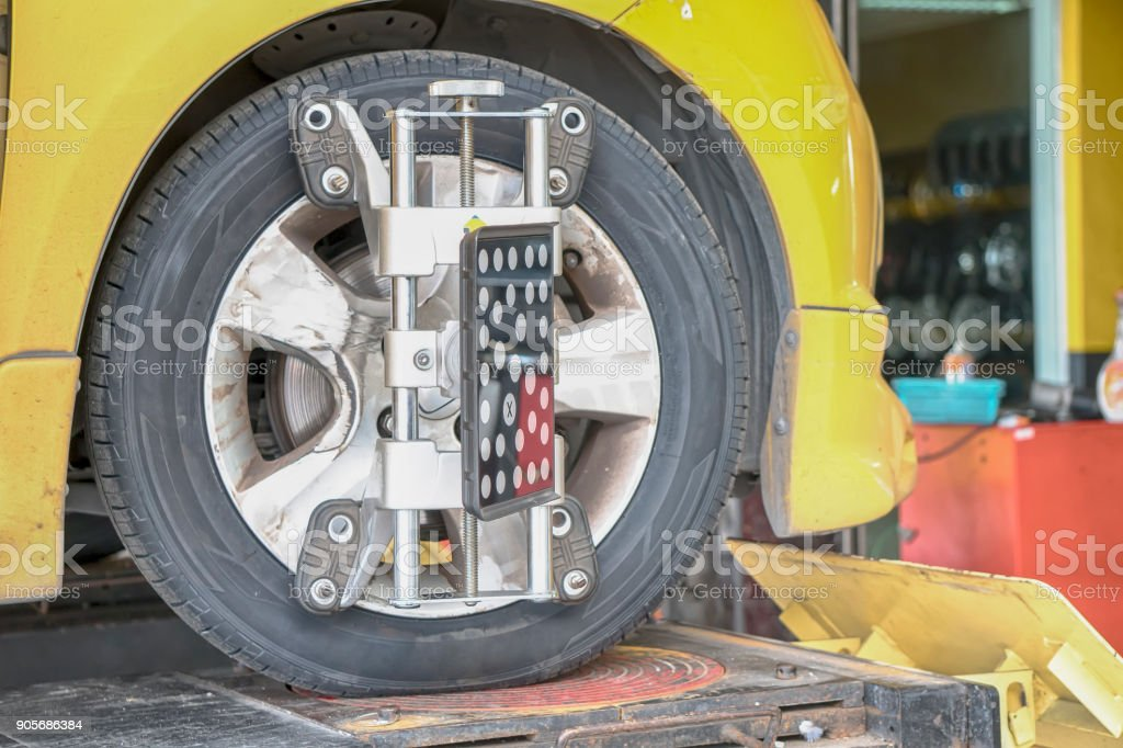Car Steering Wheel Balancer Calibrate with laser reflector attach on each tire to center driving adjust stock photo