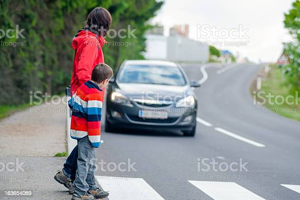 Mother and son passing a street when a car coming