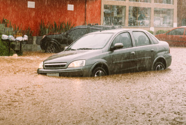 Car stuck in parking lot during a flash flood stock photo