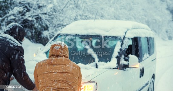 Car stuck in the snow on the road, people trying to take it off.Transportation concept.