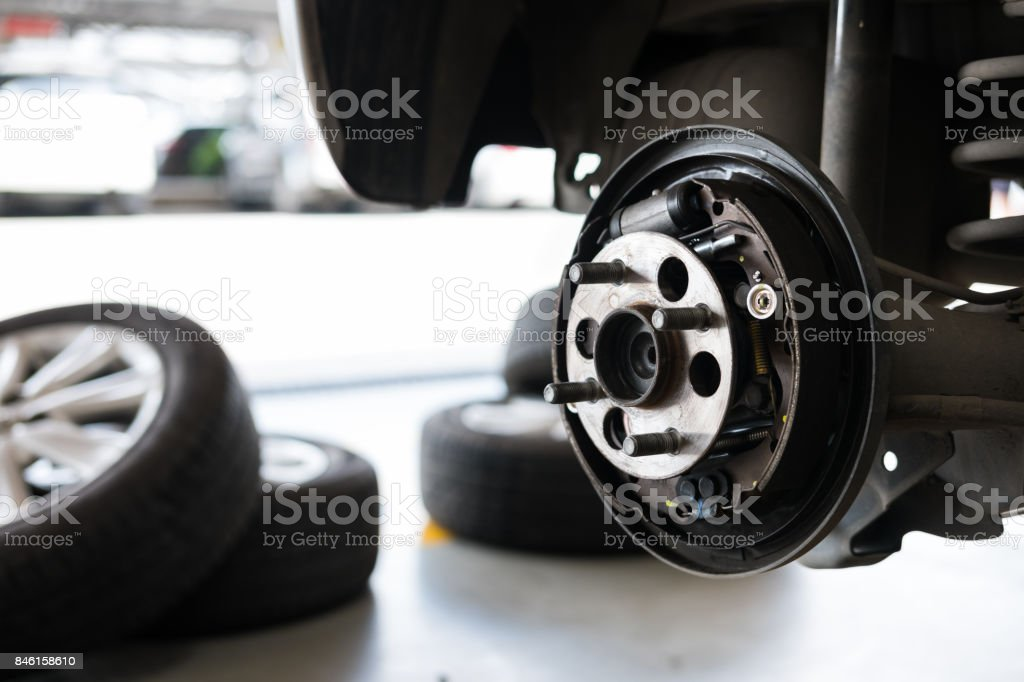 car suspension & bearing of wheel hub in auto service maintenance. Car lift up by hydraulic, waiting for tire replacement in garage. punched wheel concept stock photo