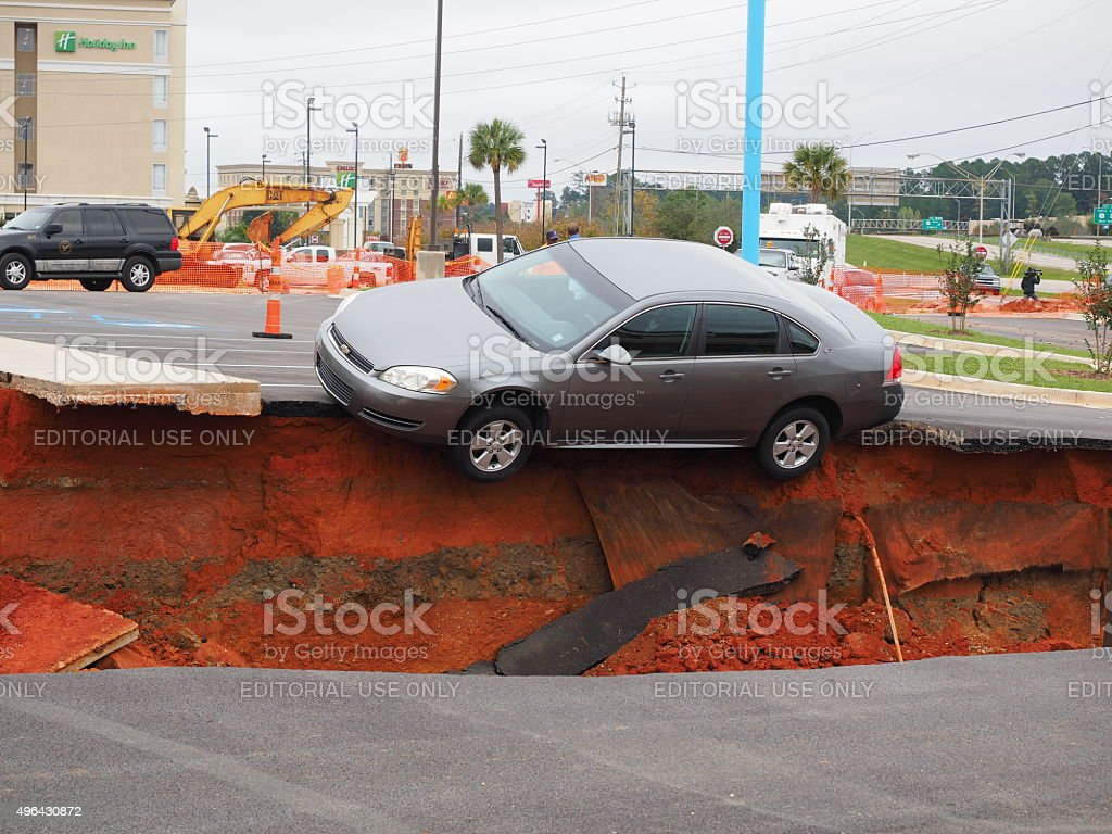 Car Teeters on Edge of Meridian Mississippi Sink Hole stock photo