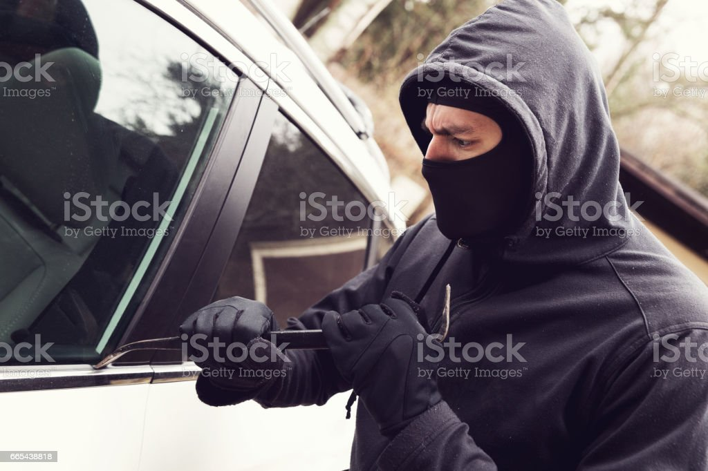 car theft - thief trying to break into the vehicle stock photo
