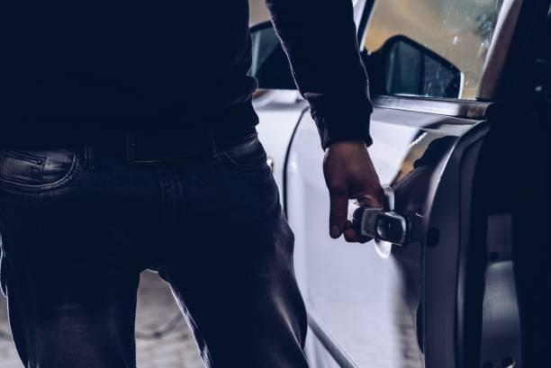 Car thief opening stolen car doors stock photo