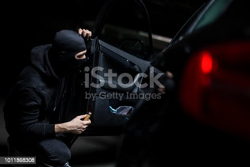 Burglar opening a car door. Unrecognizable Caucasian male wearing a balaclava.