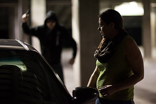 Car Thief Car Thief Hiding behind a Car at Night - Stock Image creepy stalker stock pictures, royalty-free photos & images