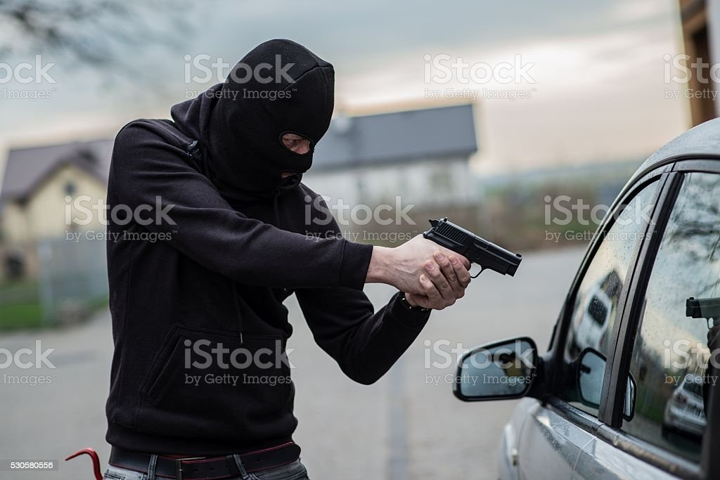 car thief pointing a gun at the driver stock photo