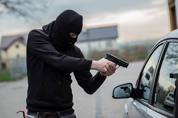 car thief pointing a gun at the driver - killer stock pictures, royalty-free photos & images