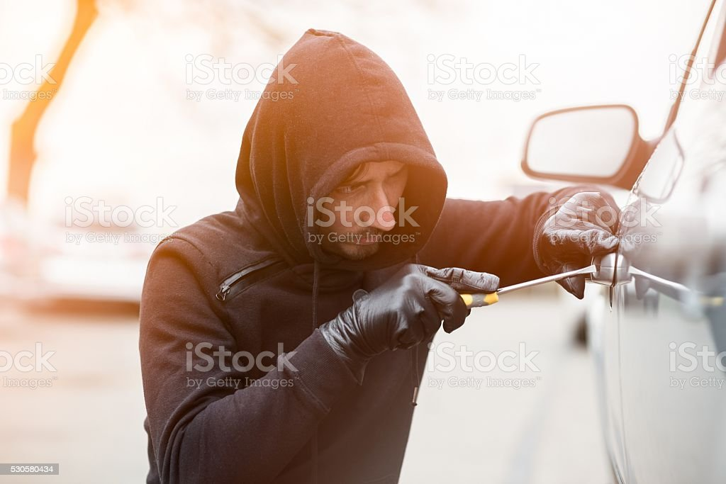 Car thief trying to break into a car with a screwdriver. Car thief,...