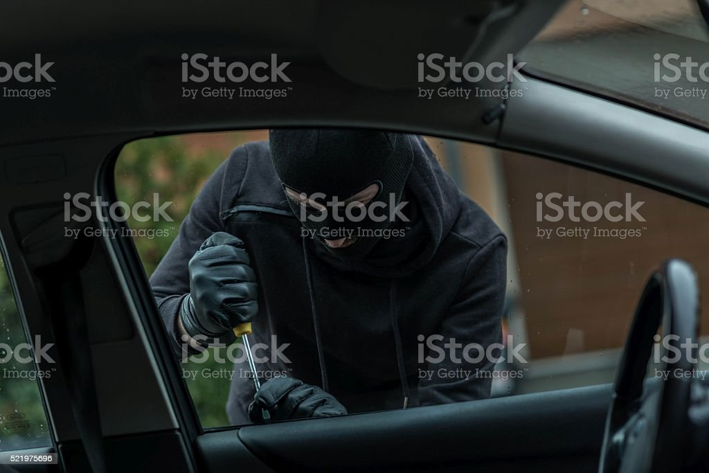 Car thief trying to break into the car stock photo