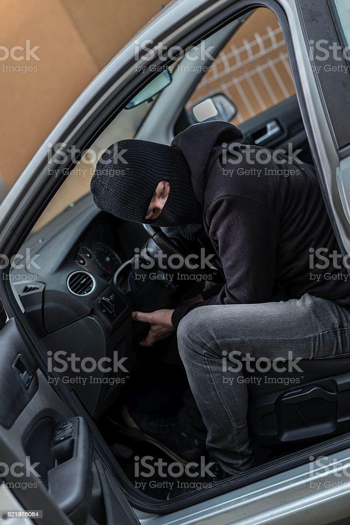 Car thief  trying to run a car. stock photo