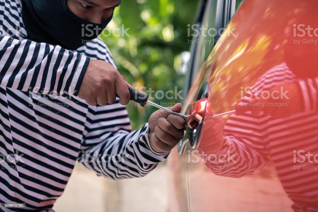 Ladrón de coches tratando de desbloquear un coche con destornillador - Foto de stock de Abierto libre de derechos