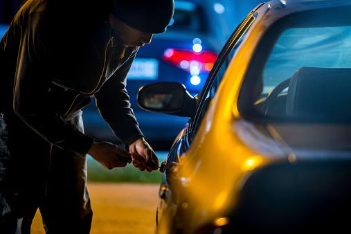 Car thief stealing a car.