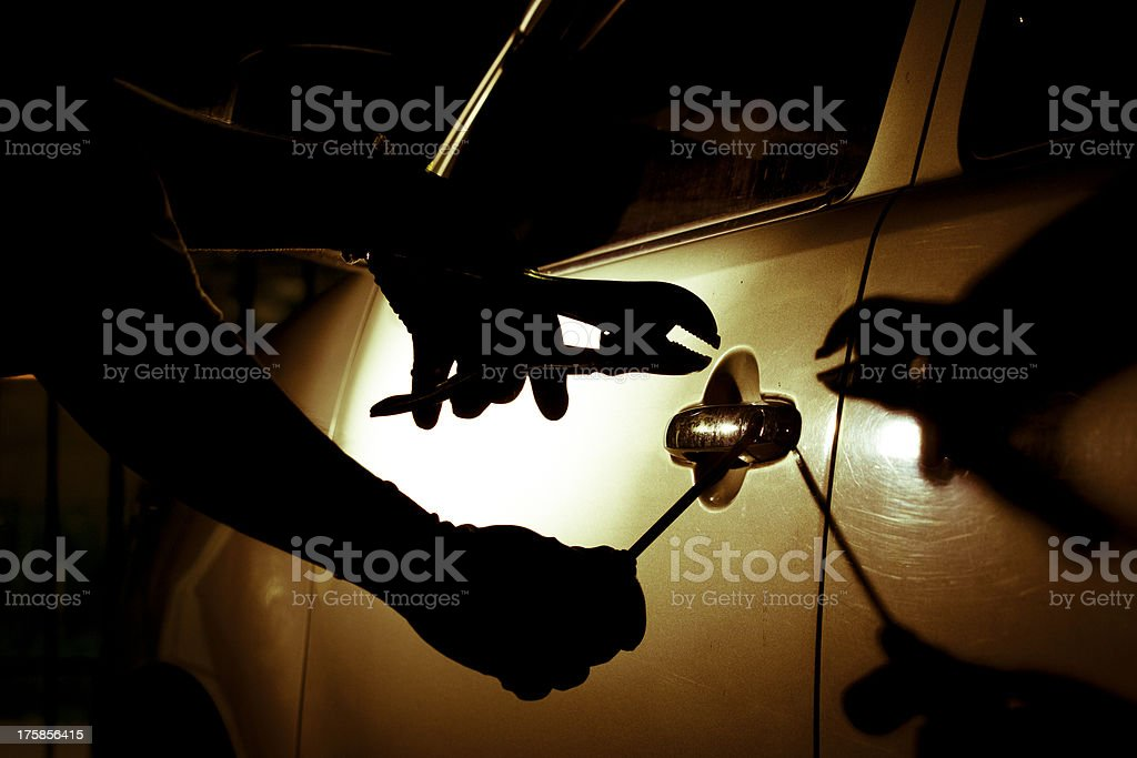Car thief using a tool to break into car. stock photo