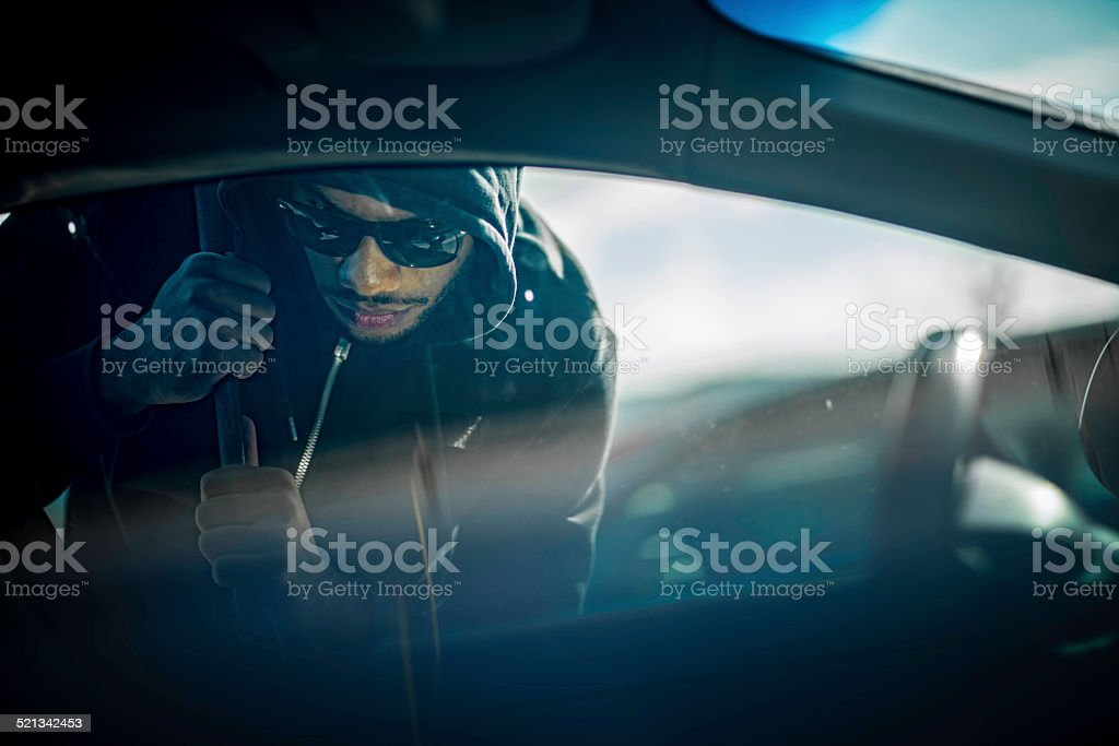 Car Thief Using a Tool to Break into Car stock photo