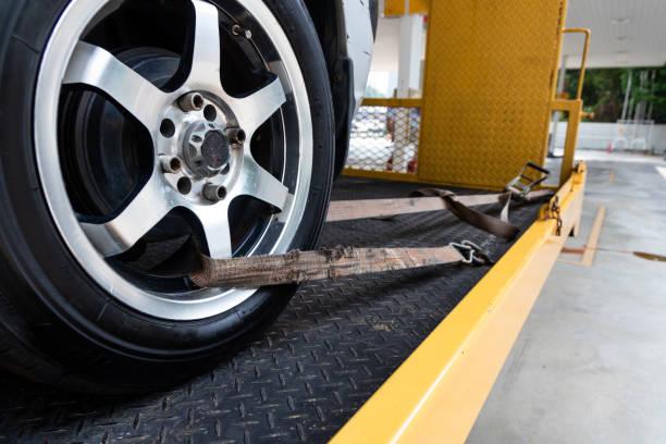 auto mit sicherheitsgurt auf flachbett-schleppwagen gebunden - pickup trucks stock-fotos und bilder
