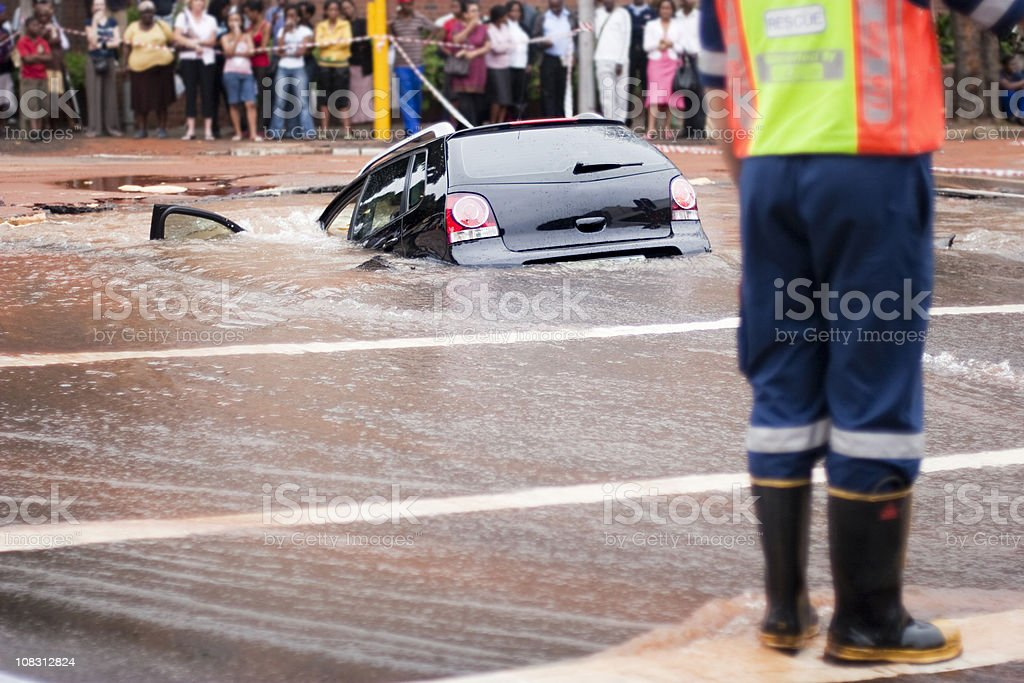 Car tips into flooded pothole, rear view royalty-free stock photo