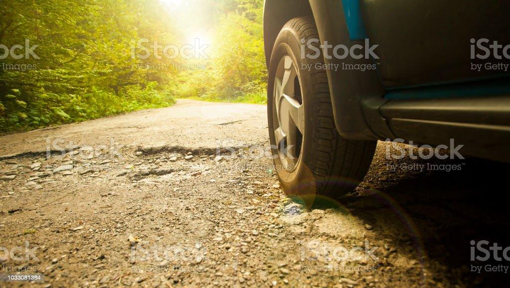neumático de coche y carretera dañada agrietada - Foto de stock de Accidente de automóvil libre de derechos