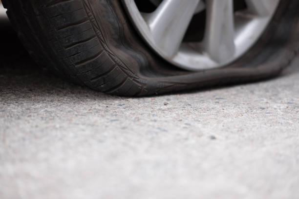 Auto-Reifen-Leck wegen Nagel schlagen. Reifenpanne unterwegs. Glätten Sie durchbohrte Rad – Foto