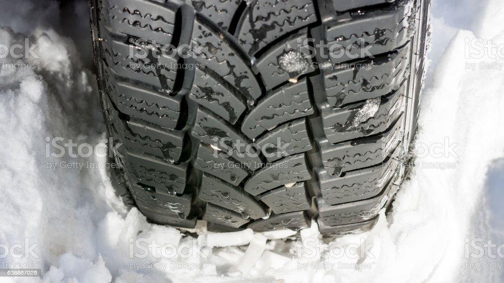 Car Tire on the Snowy Road. Winter Driving Conditions. stock photo