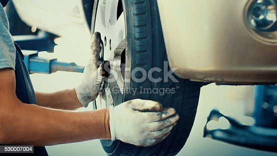 Closeup of unrecognizable male mechanic replacing car tire on front right hand wheel at a workshop. He's using pneumatic screwdriver while the car is lifted on a car jack. Side view.