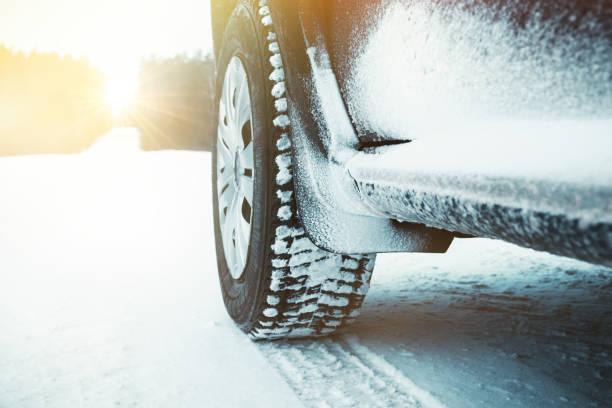 autobanden bedekt met sneeuw op winter weg door bos op zonnige dag. - tractieapparaat stockfoto's en -beelden
