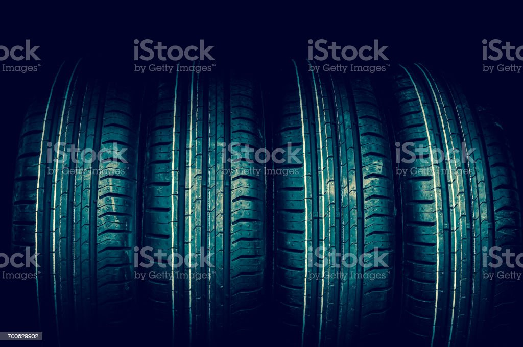 Car tires in row isolated on black stock photo